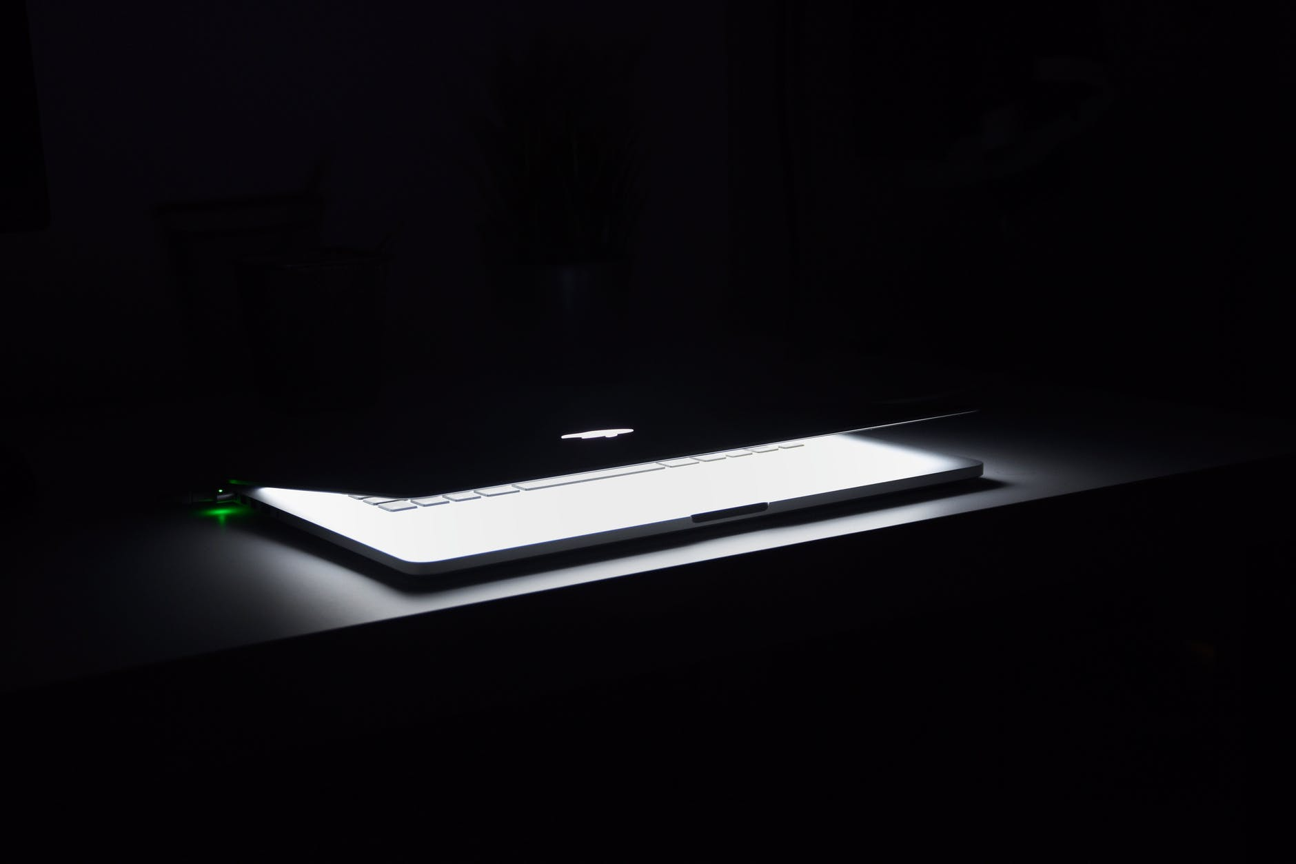 photography of macbook half opened on white wooden surface